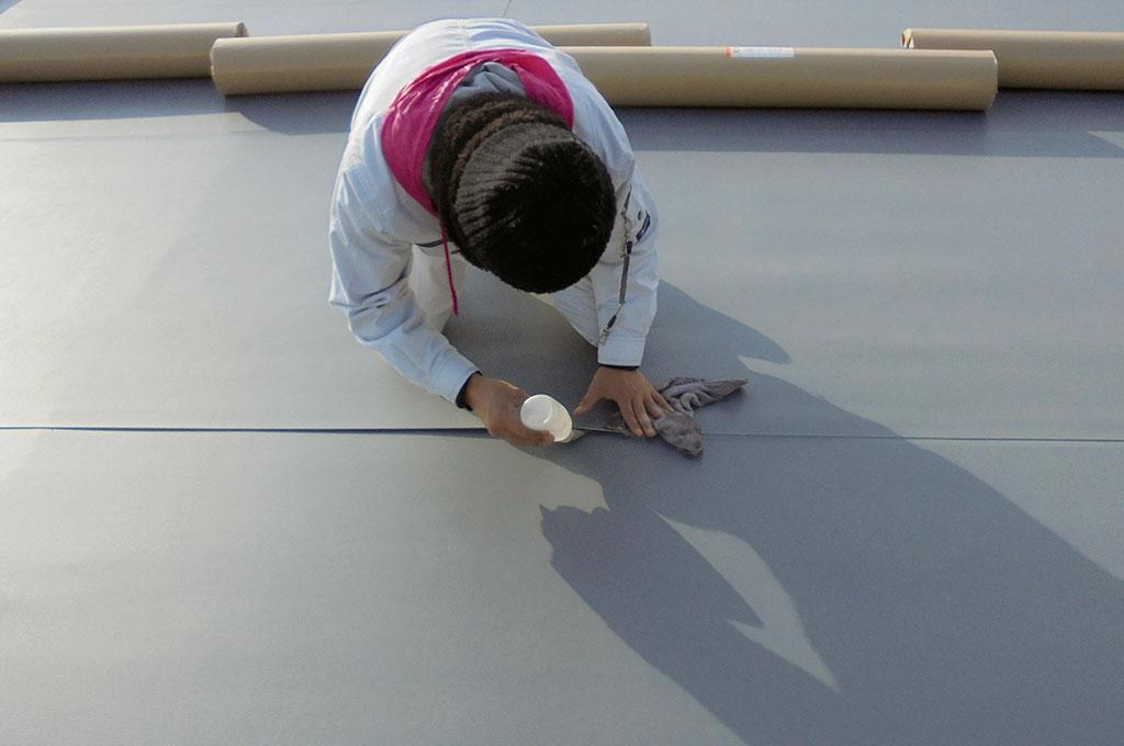 平場塩ビシートの重なりを熱風機や融着材を使って接合している写真