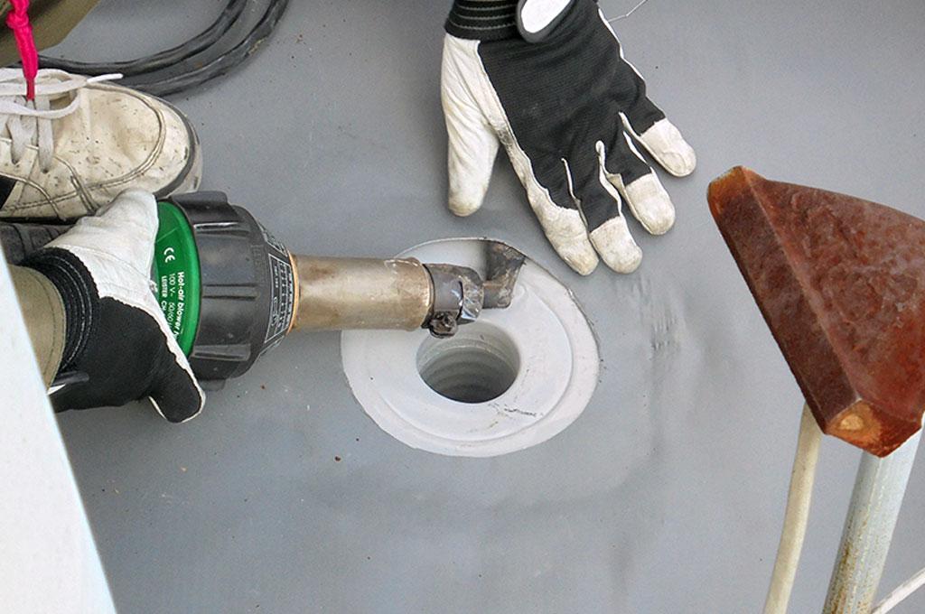 平場塩ビシートと塩ビ改修用ドレンを熱風機で接合している写真