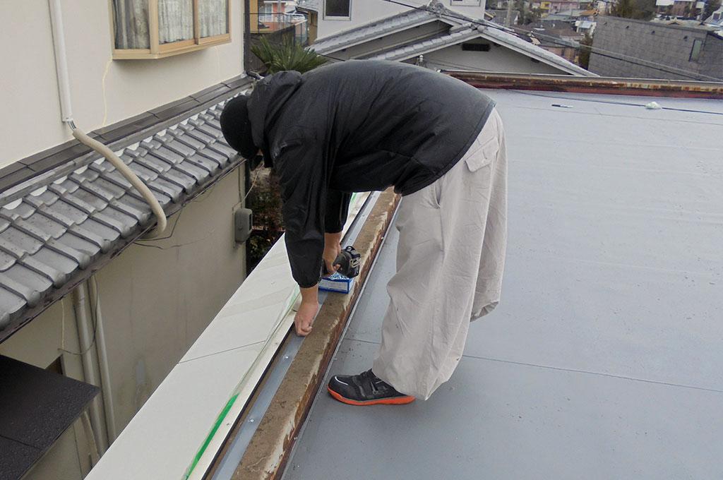 笠木天端に塩ビ鋼板を施工している写真