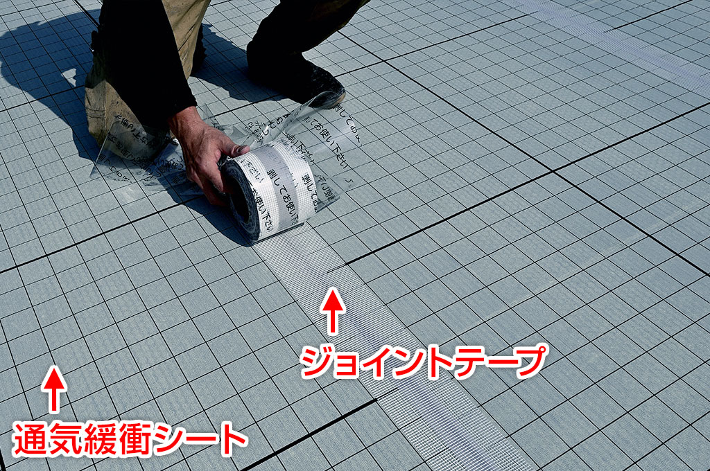 通気緩衝シートの端部を、ジョイントテープで貼り付けている写真です。