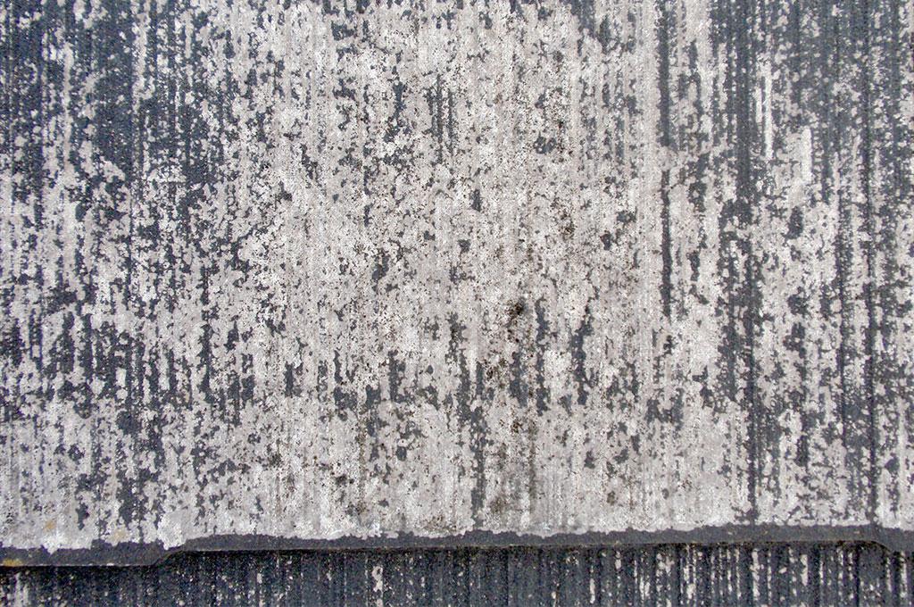 経年劣化により黒色が褪色し、カラーベスト表面基材が剥き出しになっている写真です。