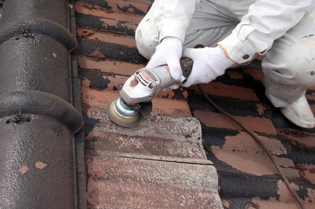 モニエル瓦屋根の旧塗膜をディスクサンダーで取り除いています。