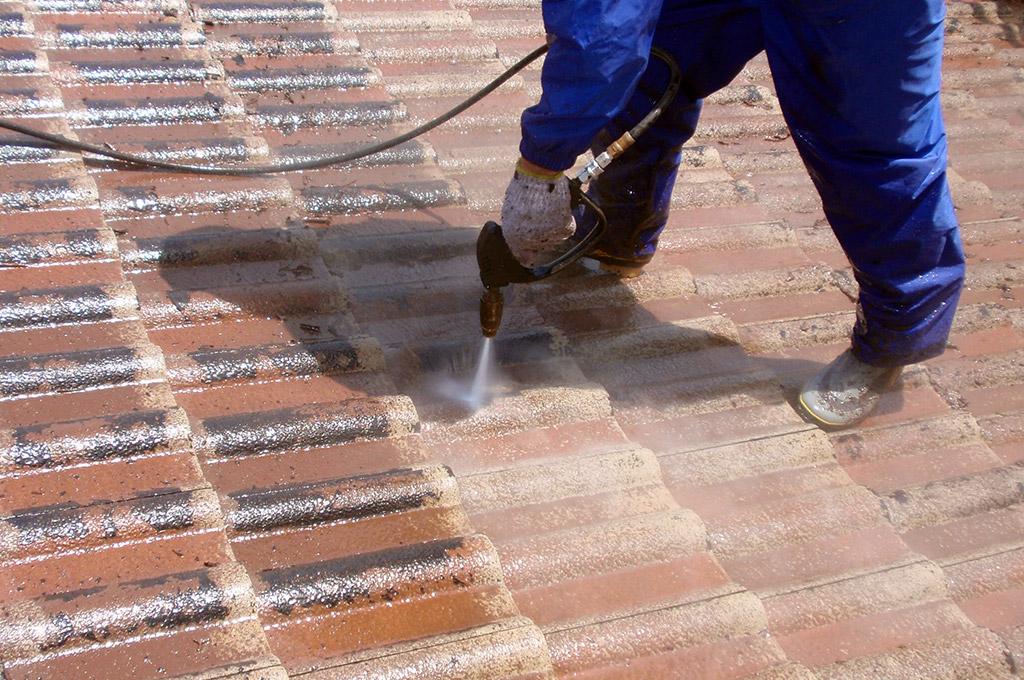 モニエル瓦屋根の旧塗膜と着色スラリーを高圧洗浄機では取り除いています。
