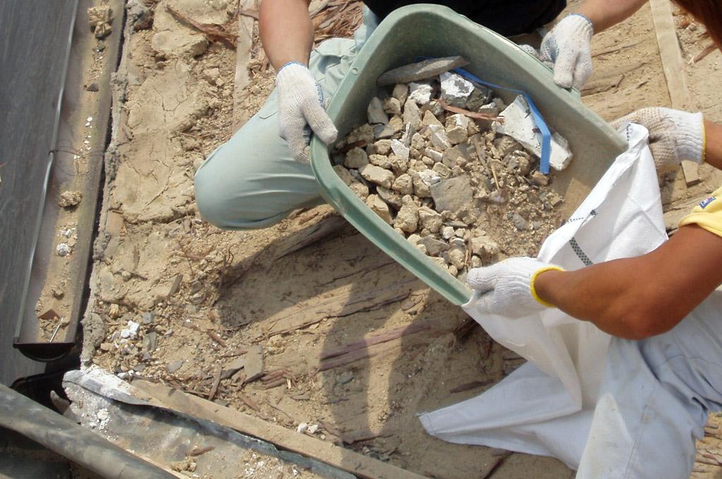 付帯工事:土や細かな瓦など飛散しない様に土嚢袋に入れて降ろします。